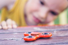 Young boy play with fidget spinner stress relieving toy. Selective focus royalty free stock photos
