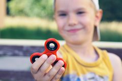 Young boy play with fidget spinner stress relieving toy. Selective focus stock photo