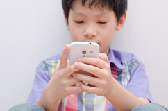 Young boy play game on smartphone Royalty Free Stock Images