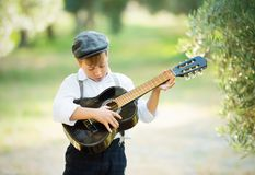 Young boy play on guitar at home at sunny day stock photography