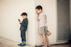 Young boy play smartphone compare with poor boy Royalty Free Stock Images