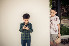 Young boy play smartphone compare with poor boy Royalty Free Stock Image