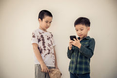 Young boy play smartphone compare with poor boy Stock Photos