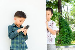Young boy play smartphone compare with poor boy Royalty Free Stock Photos