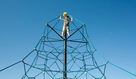 Young boy in a play structure. Young boy in a pyramidal play structure Stock Photography