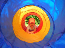 Young boy in play-tunnel. My son marc, 2-years-old, playing in the garden and crawl through the playing-tunnel Royalty Free Stock Photography