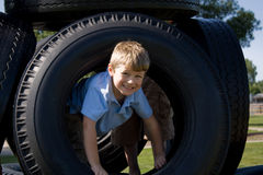Young Boy at playground. Young Boy playing on tires at playground Stock Photography
