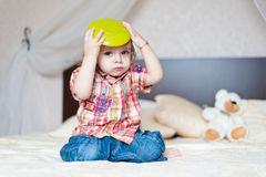 Young boy playing. On bed holding plate over his head Royalty Free Stock Photo