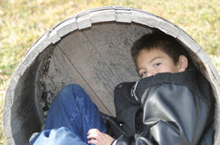 Young Boy Playing. A young boy playing inside a wood barrel Stock Photo