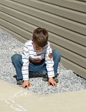 Young boy playing. Young boy playing with decorative rocks along side garage and sidewalk Stock Images