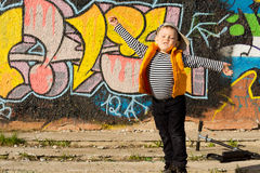 Young boy playing aeroplanes. Standing with his arms outspread and face turned up to the sun in front of a wall covered in bold geometric graffiti designs Royalty Free Stock Photo