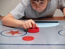 Young boy playing air hockey Royalty Free Stock Images