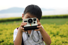 Young boy playing around with retro instant camera Royalty Free Stock Images