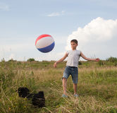 Young boy playing with a ball outdoors Stock Image
