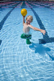 Young boy playing with ball in swimming pool Stock Photo