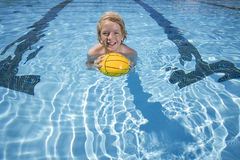 Young boy playing with ball in swimming pool royalty free stock image