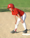 Young Boy Playing Baseball. Child playing little league baseball. He is on first base Royalty Free Stock Images