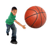 Young Boy Playing Basketball. Young African American boy playing basketball - Selective focus on ball Royalty Free Stock Photo