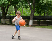 Young boy playing basketball. Young boy having fun playing basketball outdoors Royalty Free Stock Images