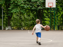 Young boy playing basketball. Young boy having fun playing basketball outdoors Royalty Free Stock Photo