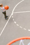 Young boy playing basketball. In an outdoor court top view Stock Photos