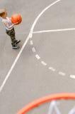 Young boy playing basketball stock photos