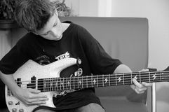 Young boy playing bass. Young boy sitting in a chair playing his bass in black and white Stock Photography