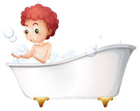 A young boy playing at the bathtub while taking a bath Royalty Free Stock Photography