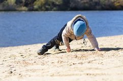 Young boy playing on beach sand at the coast Stock Image