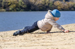 Young boy playing on beach sand at the coast Royalty Free Stock Images
