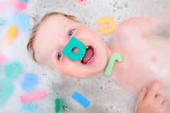 Young boy playing in bubble bath with foam letters. Young boy playing in bath with a foam letter on his face and laughing royalty free stock photo
