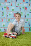 Young boy playing with car on the carpet Stock Images