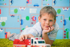 Young boy playing with car on the carpet Stock Photography
