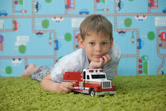 Young boy playing with car on the carpet Royalty Free Stock Images