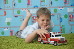 Young boy playing with car on the carpet Stock Photo