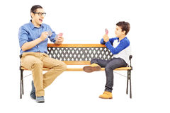 Young boy playing cards with his older cousin seated on bench Stock Photos