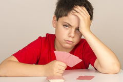 Young boy playing cards Stock Images