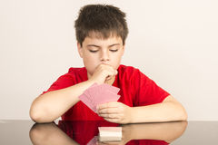 Young boy playing cards. Thoughtful young boy playing cards Stock Photos