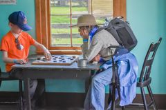 Young Boy Playing Checkers with Grandma. A young boy plays a game of checkers with his grandmother while visiting Old World Wisconsin in Eagle, WI stock image
