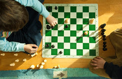 Young boy playing chess on floor. Looking down on young boy playing chess on floor at home royalty free stock photography