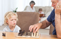 Young boy playing chess with his grandfather Royalty Free Stock Images
