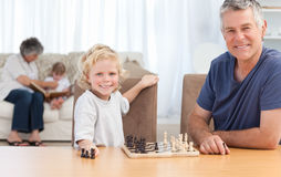 Young boy playing chess with his grandfather Stock Photography