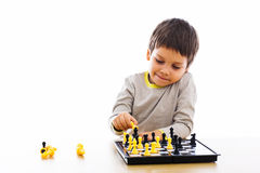 Boy playing chess. Young boy playing with chess pieces by himself Royalty Free Stock Images