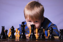 Young boy playing chess. A young boy sits in front of a chess board looking at you through the pieces royalty free stock image
