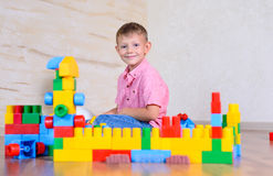 Young boy playing with colorful building blocks. Creating a robot and train engine turning to smile at the camera Royalty Free Stock Photo