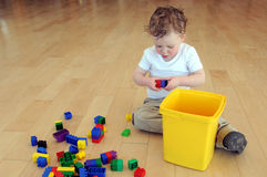 Young boy playing with coloured blocks Stock Photos