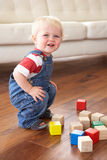 Young Boy Playing With Coloured Blocks At Home. Smiling At Camera royalty free stock photo