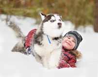 Young boy playing with the dog in the snow Stock Photo