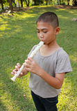 Young boy playing flute in park Stock Photos