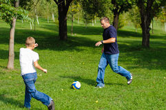 Young boy playing football with his father. Outdoors Royalty Free Stock Photo